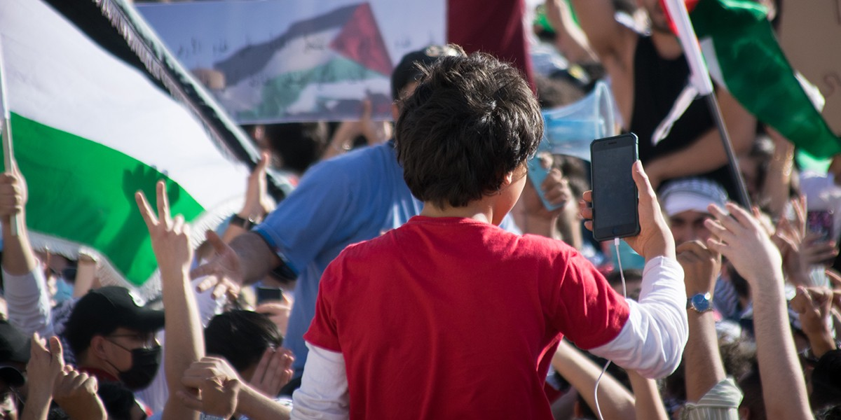 Child looks at phone in crowd with Palestinian flags